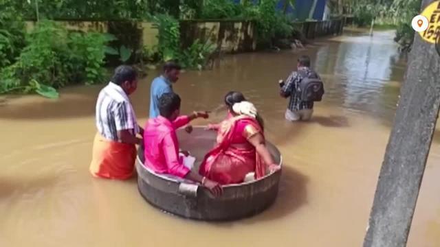 عروسان هنديان يستقلان إناء طهي عملاقا إلى موقع زفافهما بسبب الفيضانات